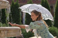 Девушка на фонтане с белым зонтиком Стоковые Изображения