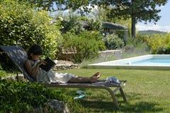 Девушка на чтении recliner стоковые изображения rf