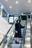 Девушка на эскалаторе в большом магазине Стоковые Фото