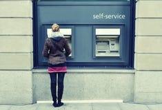 Девушка на ATM стоковые фотографии rf