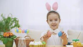 Девушка немногого милая и прелестная усмехающся и играющ с яйцами красочного цыпленка в его руках Праздник пасхи концепции видеоматериал