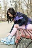 Девушка носит коньки ролика сидя на скамейке в парке Стоковое Изображение