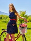 Девушка нося голубые sundress едет велосипед с корзиной цветков Стоковая Фотография RF