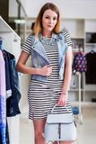 Девушка нося striped платье, жилет джинсовой ткани и сумку от собрания лета в магазине модной одежды Стоковое Изображение RF