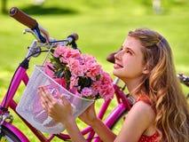 Девушка нося sundress едет велосипед с корзиной цветков Стоковое Изображение RF