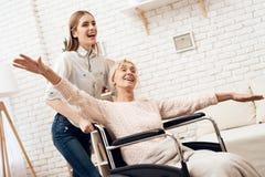 Девушка нянчит пожилую женщину дома Девушка едет женщина в кресло-коляске Женщина чувствует как летание Стоковые Изображения RF