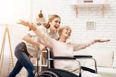 Девушка нянчит пожилую женщину дома Девушка едет женщина в кресло-коляске Женщина чувствует как летание Стоковое Фото