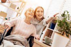 Девушка нянчит пожилую женщину дома Девушка едет женщина в кресло-коляске в живущей комнате Стоковая Фотография RF