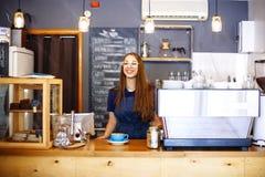 Девушка добавляет молоко к чашке с кофе в кафе Barista молодой женщины работая в кофейне Стоковое Изображение RF