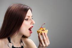 Девушка обгрызая торт Стоковое Фото
