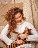Девушка обнимает кота Бенгалии Стоковые Изображения RF