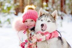 Девушка обнимая лайок в лесе зимы Стоковая Фотография RF