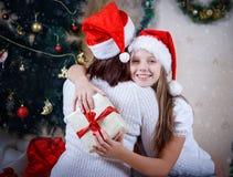 Девушка обнимая ее мать на рождестве стоковая фотография