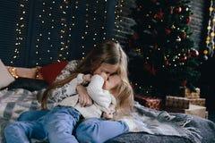 Девушка обнимая и целуя маленькую сестру Стоковая Фотография