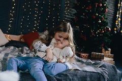 Девушка обнимая и целуя маленькую сестру Стоковые Изображения
