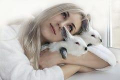Девушка обнимая 2 кроликов Стоковое Изображение RF