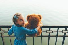 Девушка обнимая милый плюшевый медвежонка рассматривая плечо Стоковые Изображения