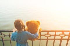 Девушка обнимая милый плюшевый медвежонка смотря к воде Стоковое фото RF