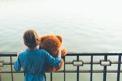 Девушка обнимая милый плюшевый медвежонка смотря к озеру Стоковая Фотография