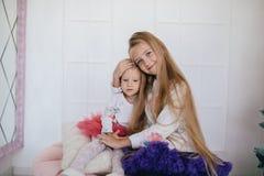 Девушка обнимая унылую маленькую сестру 2 девушки в пушистых юбках Стоковая Фотография RF