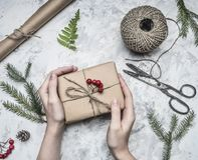 Девушка оборачивает подарок на Новый Год или рождество, рядом с ним крен бумаги, винтажных ножниц, рождественских елок хворостин  Стоковое фото RF