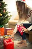 Девушка оборачивает подарок рождества Стоковая Фотография