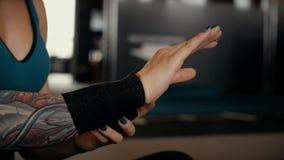 Девушка оборачивает предохранитель запястья руки вокруг ее руки