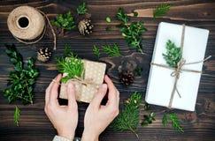 Девушка оборачивая подарок рождества Woman& x27; s вручает держать украшенную подарочную коробку на деревенском деревянном столе  Стоковые Фото