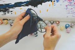 Девушка обтирает стекла с салфеткой Стоковые Изображения