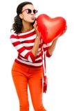 Девушка довольно смешанной гонки держа красный воздушный шар сердца Стоковые Фото