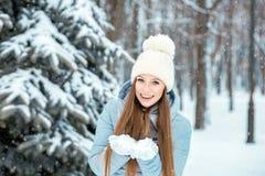 Девушка одела в теплых одеждах зимы и шляпе представляя в модели леса зимы с красивой улыбкой около рождественской елки Стоковые Фото