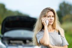 Девушка около автомобиля на дороге вызывает на мобильном телефоне Стоковые Фотографии RF