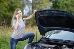 Девушка около автомобиля на дороге вызывает на мобильном телефоне Стоковое Изображение RF
