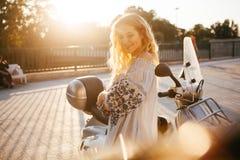 Девушка около мопеда на заходе солнца стоковое фото rf