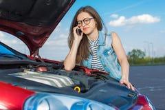 Девушка около сломленного автомобиля на проселочной дороге Стоковые Изображения