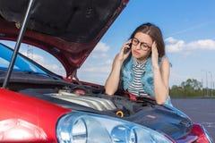 Девушка около сломленного автомобиля на проселочной дороге Стоковое Изображение