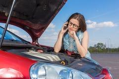 Девушка около сломленного автомобиля на проселочной дороге Стоковые Фото