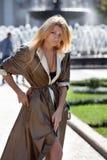 Девушка около фонтана в глянцеватом пальто осени Стоковые Фото