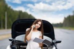 Девушка около автомобиля на дороге вызывает на мобильном телефоне Стоковое Фото