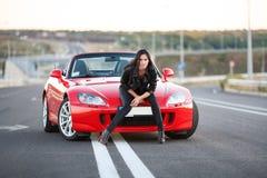 Девушка около красного автомобиля стоковые изображения