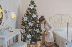 Девушка около рождественской елки с подарками Стоковая Фотография