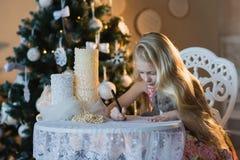 Девушка около рождественской елки с любимым кроликом игрушки пишет письмо к Санте, коробки, рождество, Новый Год, образ жизни, пр Стоковая Фотография