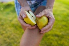 Девушка ломает яблоко в 2 части Стоковое Фото