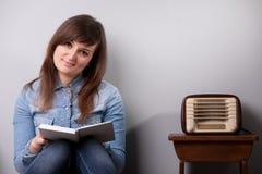 Девушка дома читая внутри ослабляет Стоковые Изображения RF
