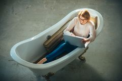 Девушка ослабляет в ванне с компьтер-книжкой держит блог Поворотливые дело и сообщение Купите онлайн и цифровой маркетинг стоковое изображение