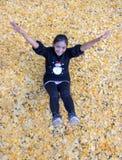 Девушка ослабляет в середине желтых листьев Стоковое Фото