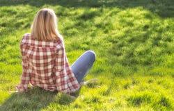 Девушка ослабляет на луге Белокурая красивая молодая женщина сидит на траве и наслаждается солнцем r r r стоковые фото