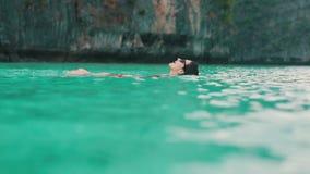 Девушка ослабляет плавать на ее назад в воду бирюзы видеоматериал