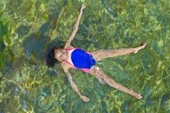 Девушка ослабляя в море стоковая фотография rf