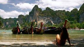 Девушка ослабляя около шлюпок длинного хвоста Таиланда на тропическом пляже сток-видео